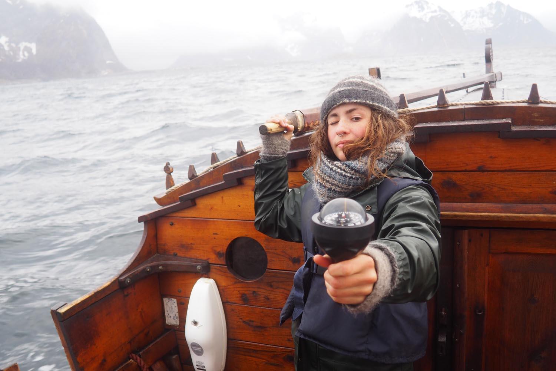Ei jente styrer trebaten mens hun tar krysspeiling med kompass for a navigere