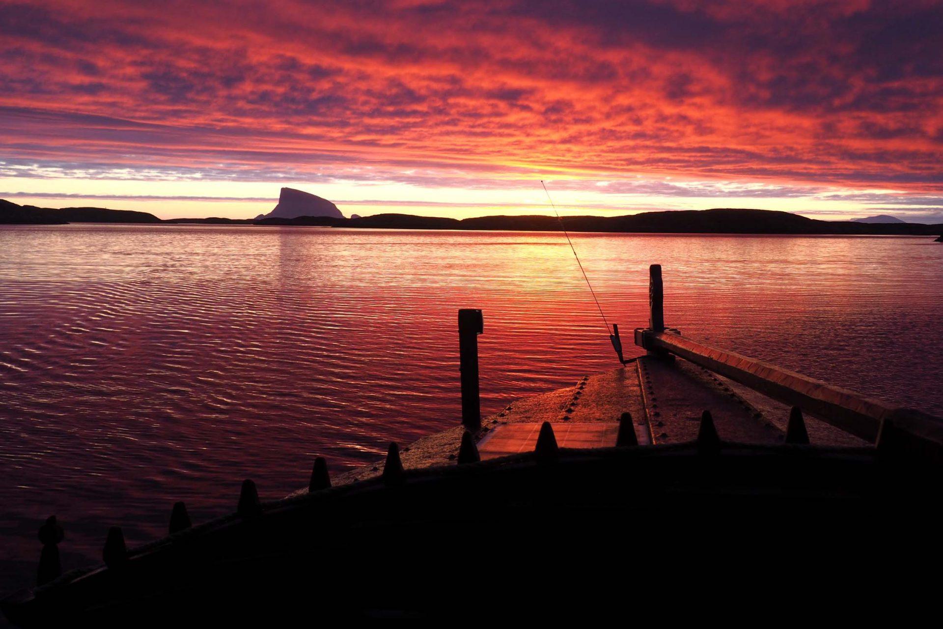 Seiling i solnedgang pa helgelandskysten. Trebat med rorgrind i forgrunnen, Lovund i bakgrunnen.
