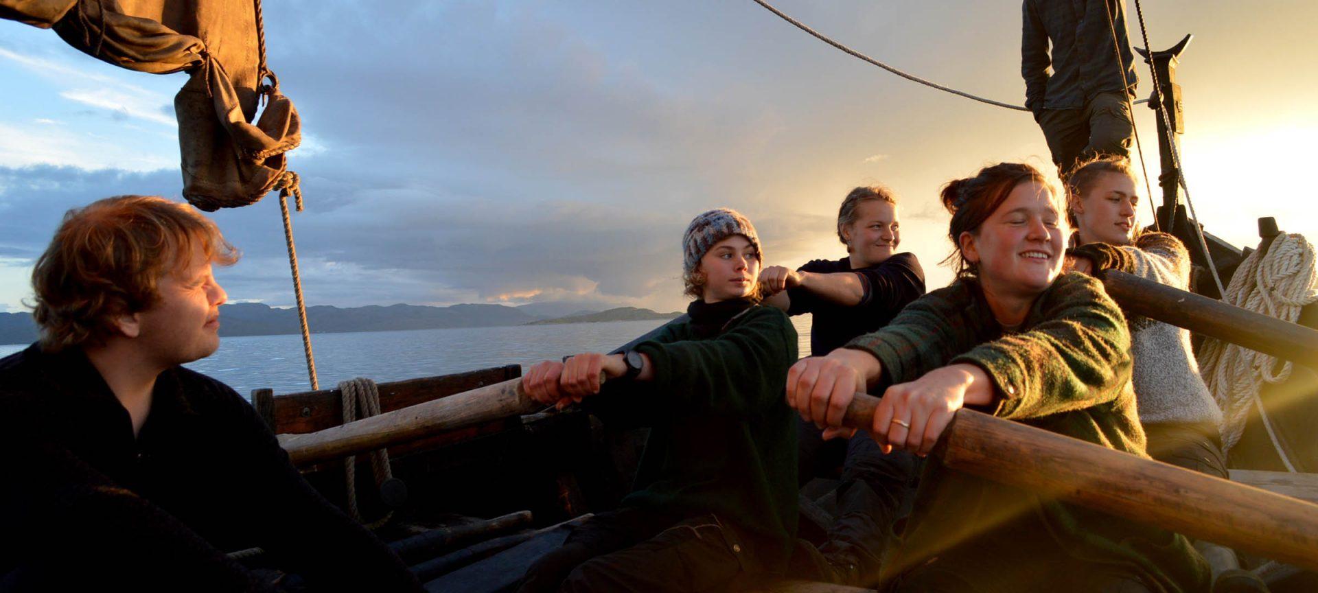 Elever på Fosen Folkehogskole ror en trebat i solnedgangen
