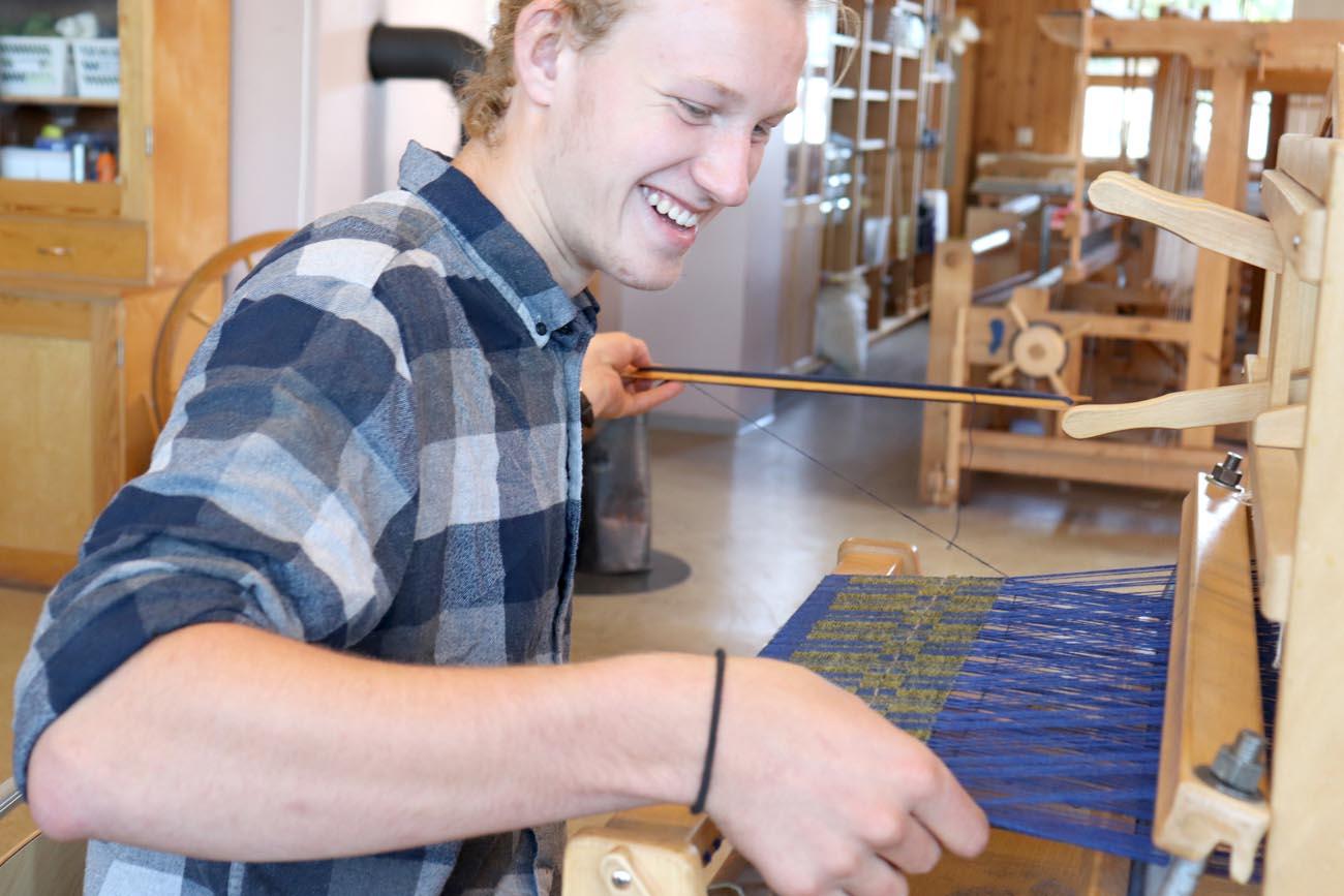 En gutt vever tavlebragd pa en bordvev